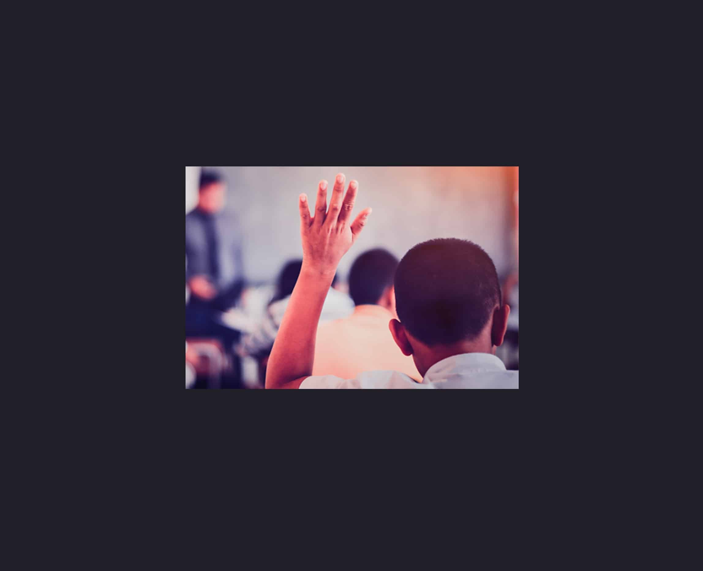 A child in classroom raising his hand